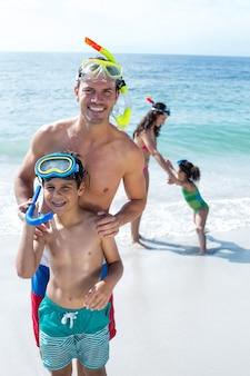 ビーチで母と娘と一緒に立っている父と息子