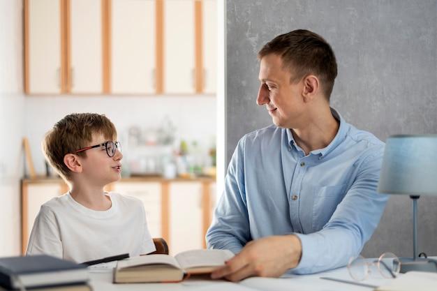 父と息子は家で学校の科目を勉強します。若い先生が生徒に教えます。ホームスクーリング。