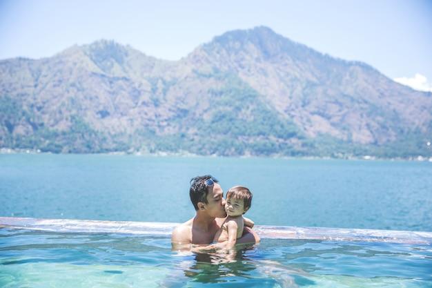 プール、湖、山で泳いでいる父と息子