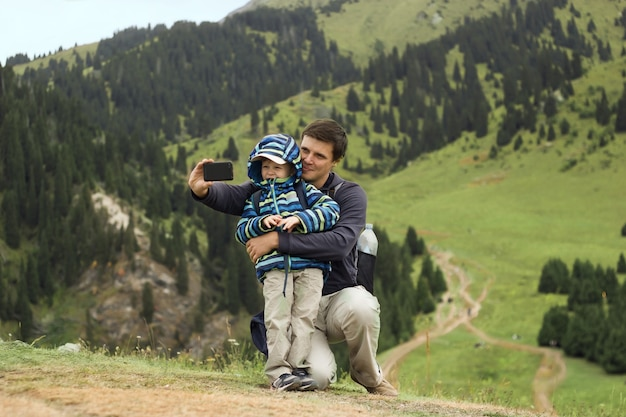 Отец и сын делают селфи, размышляя в горах, семейное путешествие