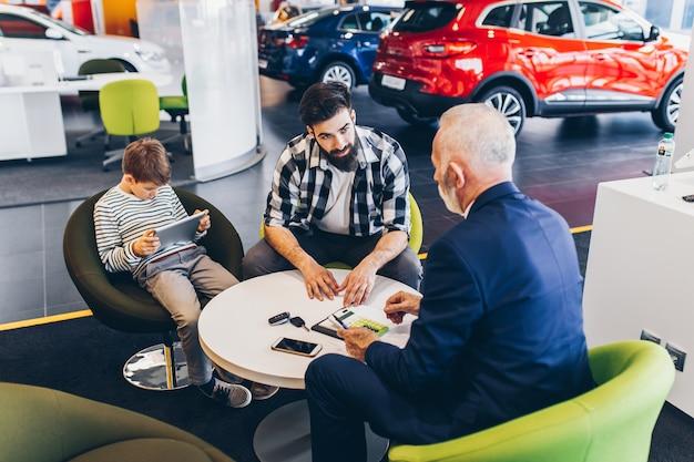 Отец и сын разговаривают с продавцом о покупке новой машины в автосалоне.