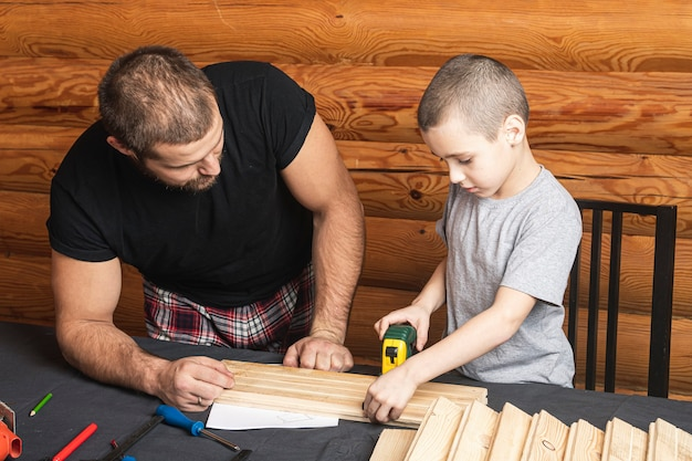 아버지와 아들이 함께 워크숍에서 나무 새집을 만듭니다.