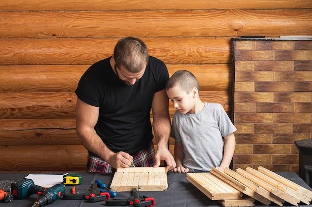Отец и сын вместе делают в мастерской деревянный скворечник