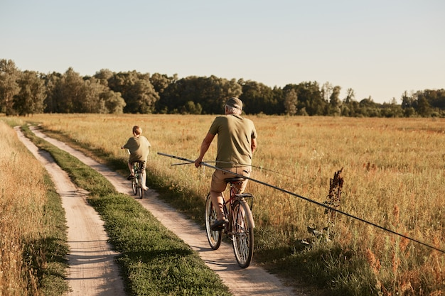 Отец и сын вместе едут на велосипедах по тропинке в поле, едут с удочками, хотят ловить рыбу, проводят солнечный день, активно отдыхая.