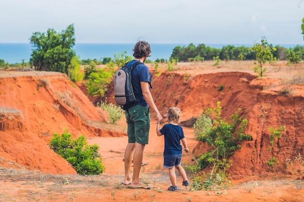 ベトナム南部のムイネー近くの赤い峡谷を旅する父と息子。子供と一緒に旅行のコンセプト。