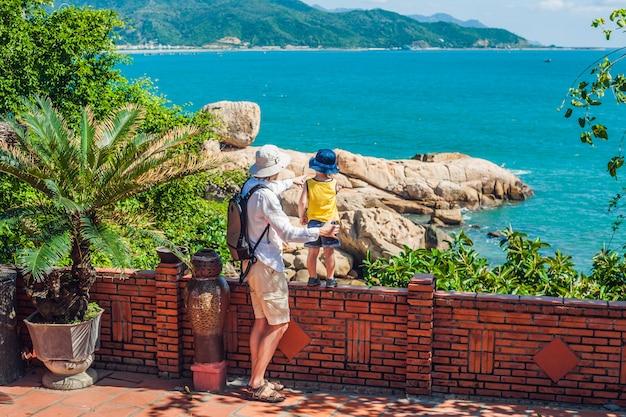 Отец и сын путешественники смотрят на мыс хон чонг, садовый камень, популярные туристические направления в нячанге. вьетнам