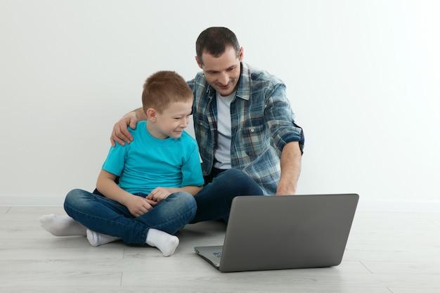 Отец и сын используя компьтер-книжку сидя на паркете совместно дома. концепция изоляции