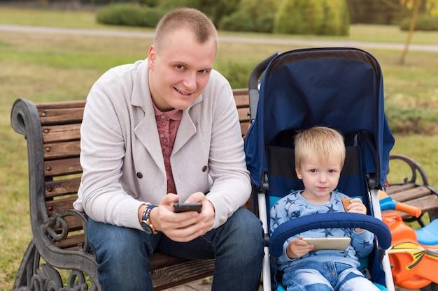 秋の公園で一緒に時間を過ごしながらスマートフォンを使う父と息子。