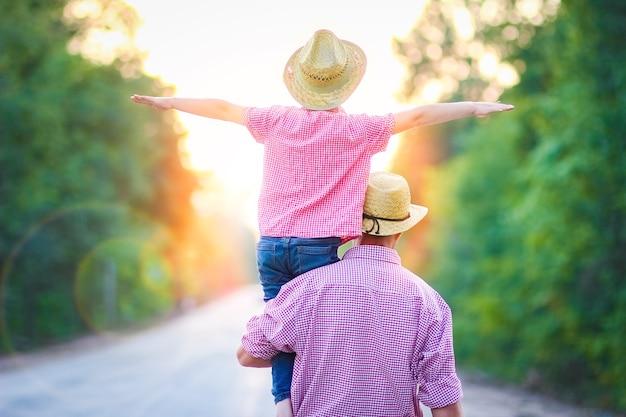 Отец и сын идут по дороге, держась за руки с чемоданом
