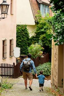 父と息子は、ドイツのヨーロッパの旧市街の通りを歩きます
