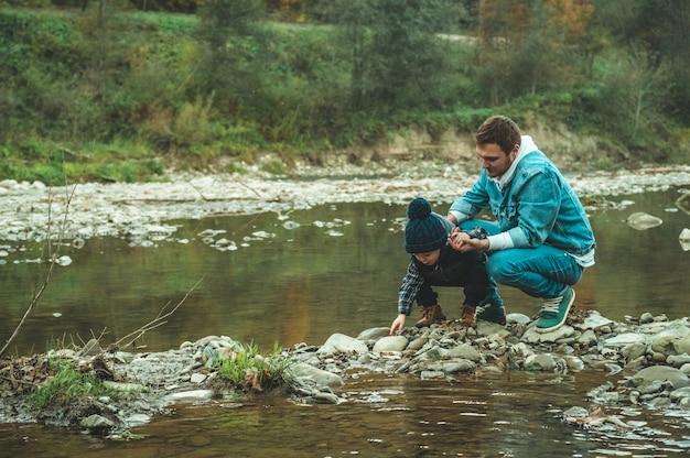 Отец и сын гуляют и играют вместе. осень в горах.
