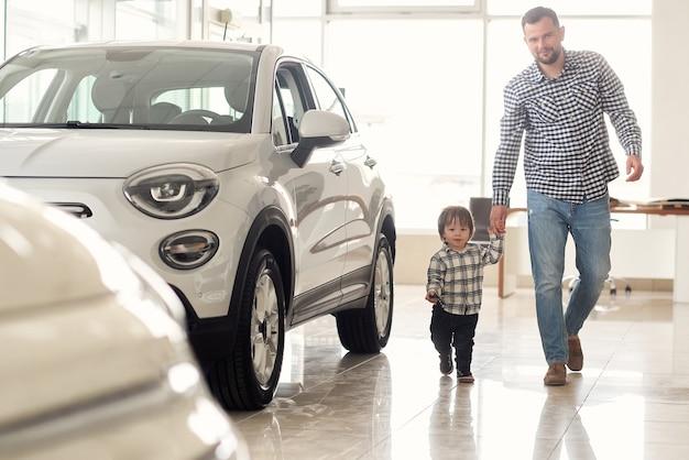 Отец и сын гуляют по большому автосалону и рассматривают новые модели автомобилей.