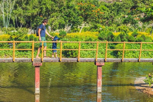 Отец и сын идут по мосту через пруд