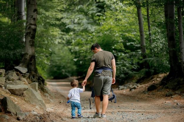 아버지와 아들이 숲에서 길을 걷고