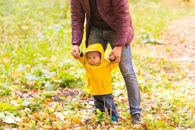 아버지와 아들이 걷고 있습니다. 도시의 가을 정원에서 아버지의 도움으로 첫 걸음을 내딛는 아기.