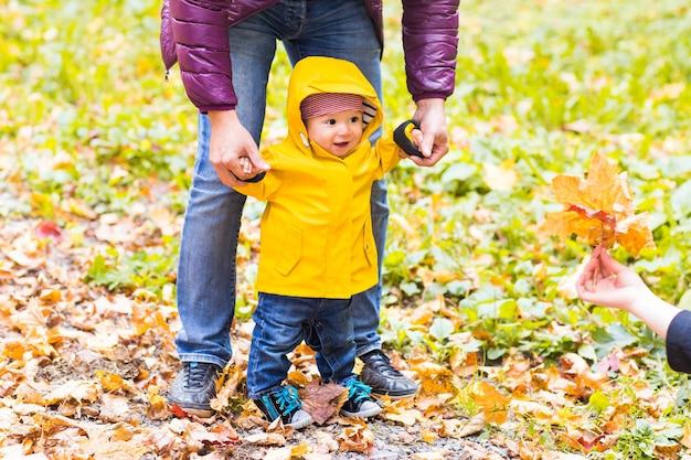 Отец и сын гуляют. ребенок делает первые шаги с помощью отца в осеннем саду города.
