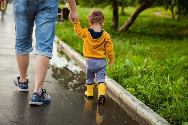 夏の日の雨の後、水たまりにゴム長靴で新鮮な空気を歩く父と息子。小さな子供が男の手を握って。