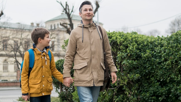 Отец и сын гуляют вместе на свежем воздухе