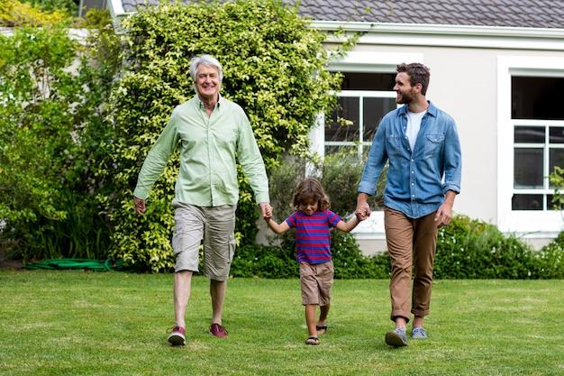 Отец и сын гуляют с мальчиком во дворе