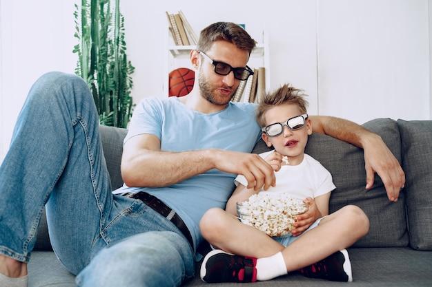 父と息子は自宅で3dメガネで映画を見て、ソファでポップコーンを食べる