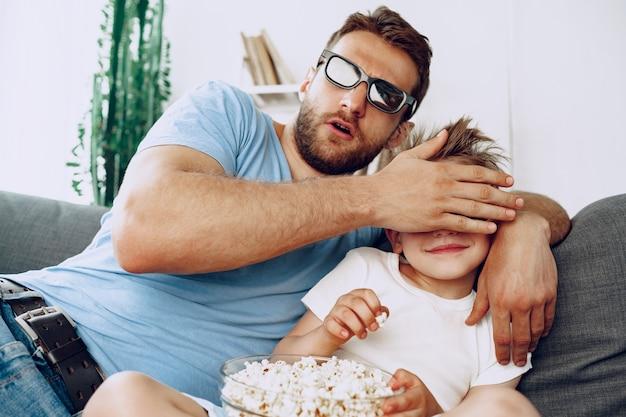 父と息子は3dメガネで自宅で映画を見て、ソファでポップコーンを食べる