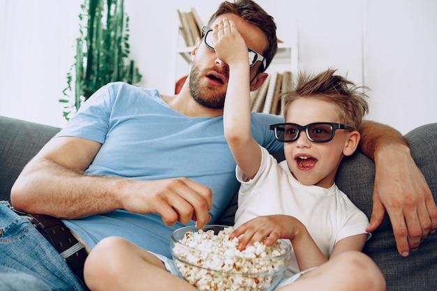 父と息子が3dメガネで家で映画を見て、ポップコーンを食べる