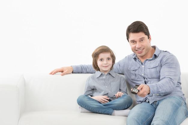 Отец и сын вместе смотрят телевизор на диване