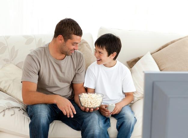 ソファーにポップコーンを食べながらテレビを見ている父と息子