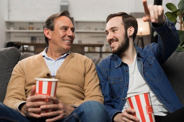 Отец и сын смотрят телевизор в гостиной