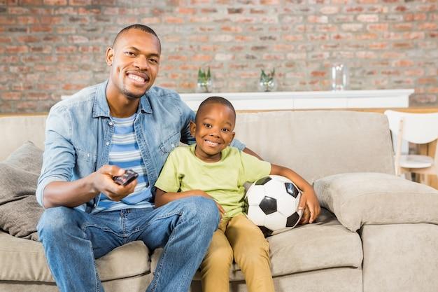Отец и сын смотрят телевизор вместе на диване