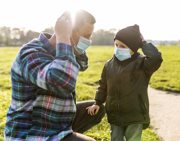 Отец и сын в медицинских масках на открытом воздухе