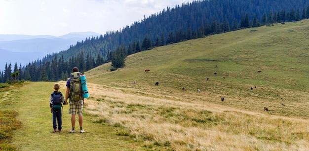 Отец и сын с рюкзаками, походы вместе в живописных летних зеленых гор. папа и ребенок стоя наслаждающся горным видом ландшафта. активный образ жизни, семейные отношения, концепция деятельности выходного дня.