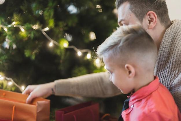 クリスマスツリーの前に鞄を持つ父と息子