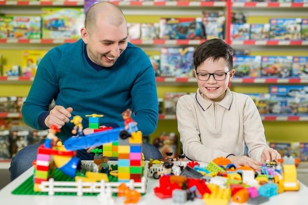 Отец и сын со счастливыми лицами создают красочные конструкции из игрушечных кубиков. папа и малыш строят из пластиковых блоков. концепция семьи и детства.