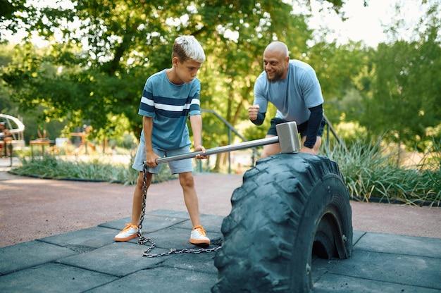 父と息子のスレッジハンマー、屋外の遊び場でのクロスフィットスポーツトレーニング。家族は夏の公園で健康的なライフスタイル、フィットネストレーニングをリードしています