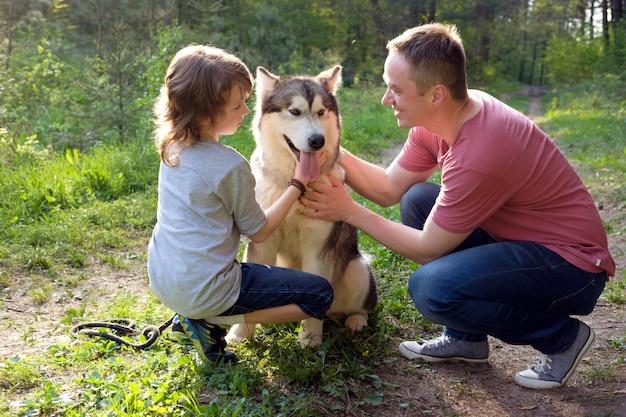 Отец и сын с собакой маламут на прогулке в лесу