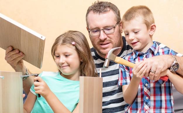 Отец и сыновья строят дома мебель.