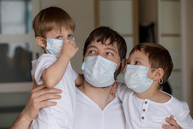 自宅で医療用マスクを着用した父と息子。セレクティブフォーカスの画像。高品質の写真