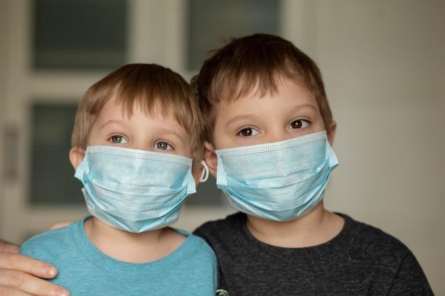 選択的な焦点と自宅の画像で医療マスクの父と息子