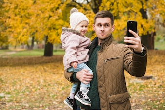 Father and toddler daughter doing selfie in autumn park