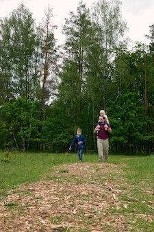 Отец и двое детей, сын и дочь в походе в лес. семейная прогулка. летнее время вместе в кемпинге. с днем отца.