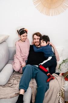 아버지와 웃 고 카메라를보고 소파에 앉아 두 아이. 다국적 가족. 실생활, 공생, 다양성, 가정의 편안함