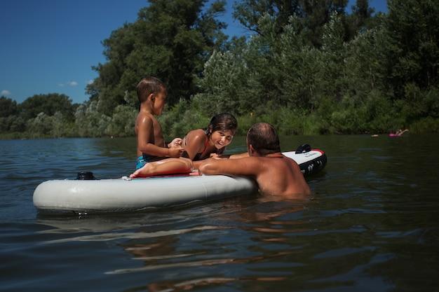 Отец и двое детей плавают на доске с веслом