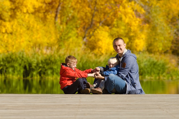 Отец и два сына играют на пирсе. осень, солнечно. вид сбоку