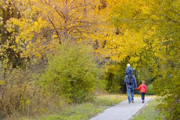 Отец и двое сыновей гуляют по осеннему парку