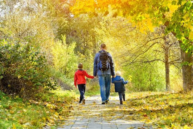 秋の森を歩く父と2人の息子。背面図