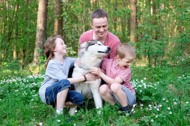 Отец и двое сыновей с собакой маламут на прогулке в лесу