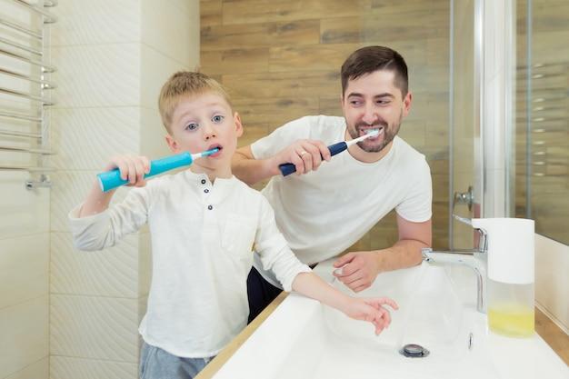 Отец и маленький сын чистят зубы утром, веселятся вместе