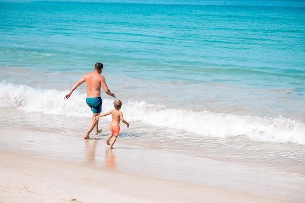 Отец и молодой сын, играя на пляже