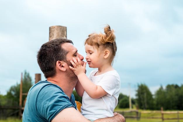 村の父と美しい女の赤ちゃん。木製のフェンスの上に座っています。娘は彼女の父親を抱きしめてキスします。優しい幸せな家族。父の日。